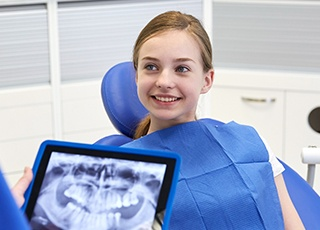 Dentist talking to girl about dental x-rays