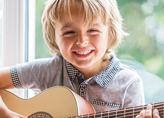 Smiling little boy playing guitar