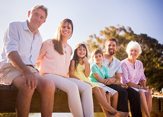 Three generations of family smiling outdoors